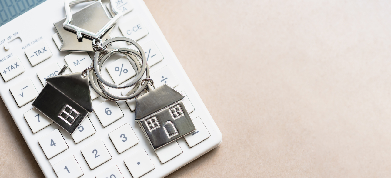 small house on keychain laying beside calculator