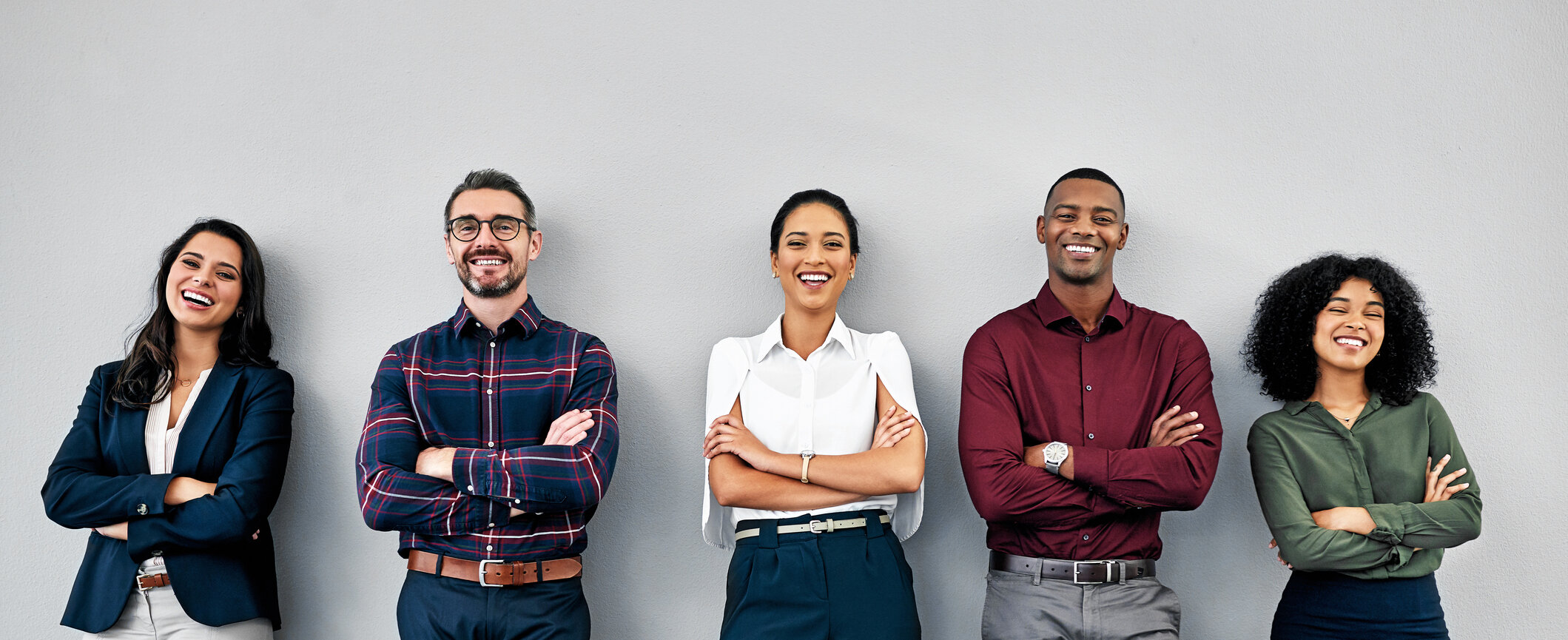 people leaning on wall smiling